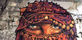 ציור גרפיטי של אישה מכוסה על קיר