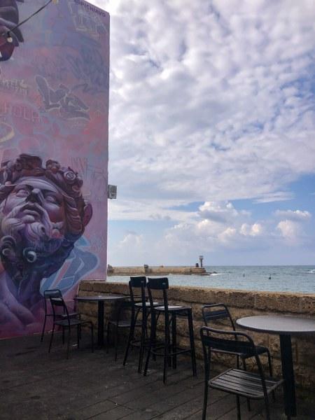 פינות ישיבה מול הים בנמל עכו ולצד גרפיטי